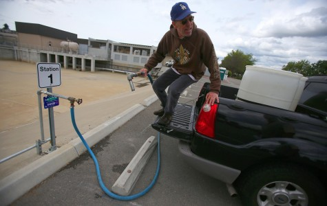 Leon Jung hops off the tailgate of his truck after filling two 55-gallon barrels with recycled water at the Dublin San Ramon Services District on April 6, 2015, in Pleasanton, Calif. Jung uses the recycled water for his lawn, garden, and flowers. (Aric Crabb/Bay Area News Group/TNS)