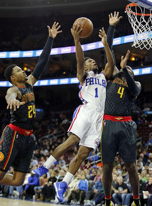 The Philadelphia 76ers' Ish Smith (1) lays-up a shot against the Atlanta Hawks' Paul Millsap, right, and Kent Bazemore during the third quarter on Thursday, Jan. 7, 2016, at the Wells Fargo Center in Philadelphia. The Hawks won, 126-98. (Yong Kim/Philadelphia Daily News/TNS)