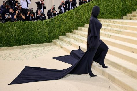 Kim Kardashian surprises the audience at the 2021 Met Gala with a head to toe black gown. Fans believe the outfit was a reference to Kanye Wests recent Donda album.